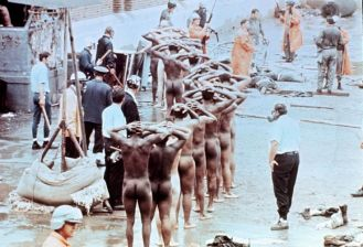 EDS NOTE: NUDITY Prisoners with their hands on their heads and stripped of all clothes are lined up after guards regained control following the Attica prison riot in Attica, New York, Sept. 1971. The riot, in which 43 were killed, lasted four days during which guards were held as hostages. (AP Photo)