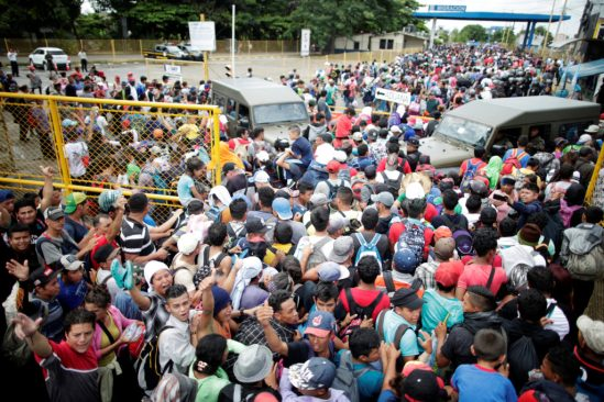 Honduran migrants, part of a caravan trying to reach the U.S., storm a border checkpoint to cross into Mexico, in Tecun Uman