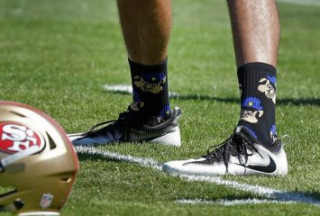 "FILE - In this Aug. 10, 2016, file photo, San Francisco 49ers quarterback Colin Kaepernick wears socks depicting police officers as pigs during NFL football training camp at Kezar Stadium in San Francisco. Kaepernick says he has been wearing socks depicting police officers as pigs in protest of ""rogue cops"" who put the community and other officers at risk. Kaepernick issued a statement on Twitter on Thursday, Sept. 1, 2016, after photos of him wearing the socks that show a pig dressed in a police hat began circulating on social media. (AP Photo/Ben Margot, File)"